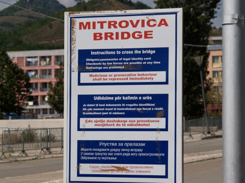 Istruzioni per attraversare il Ponte di Mitrovica. Foto scattata nel 2005. Attualmente il cartello pare sia stato rimosso. Licenza Common Sharing